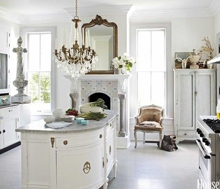 white kitchen, vintage over mantel mirror, demilune chest back with cabinets and topped with marble for island - genius