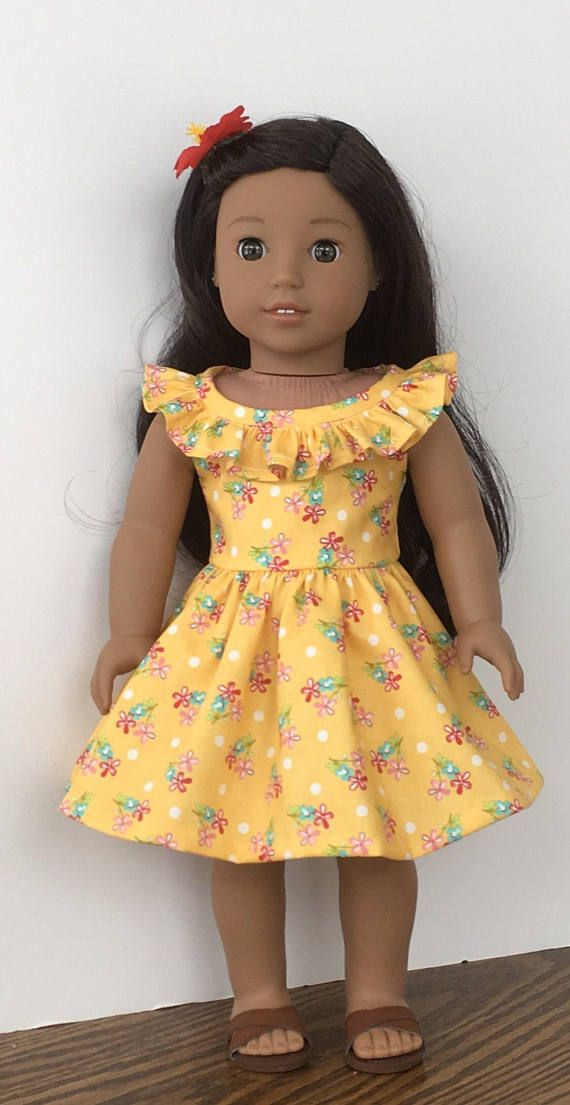 A beautiful dress for your island doll. This dress is made from a yellow cotton fabric that has a red,pink and aqua flower print print on it. The bodice is fully lined. The neckline has a gathered ruffle sewn to it. Snaps are sewn to the back bodice to close the dress. The skirt is