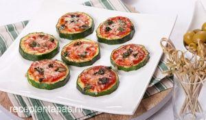 Lekkere en gezonde mini pizza's van plakjes courgette belegd met tomaat, kaas en basilicum