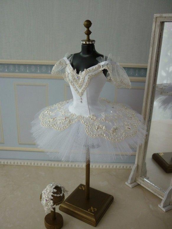 こちらは受注後制作の作品の為、発送までに1ヶ月ほどお時間をいただきます。本物のバレエ衣装チュチュを部屋に飾り毎日眺めていたい、そんな思いから作り始めました。1/6ドールサイズのトルソーに合わせて作ったミニチュアのチュチュです。「シンデレラ」を踊るバレリーナをイメージして、白色のシャンタン生地とチュールにシルバーのレースとスワロフスキーのストーン等で飾り付けをしています。袖付きのスタイルで、肩紐は透明ゴムです。スカート部分も3段仕立てで本格的作りになっています。トルソーの高さ 約25センチスカートの巾 約14センチバービーに着せることもできます。(バービーには胸周りに少し余裕があります。)できるだけ本物のチュチュをミニチュアサイズで再現できるように、実際のチュチュの作り方を参考にパターンおこしから細部までこだわって作りました。トルソーに着せやすくするために背中は全開きになっています。トルソーに着せるため本物のクラシックチュチュ(短いスカートのチュチュ)に付いているツンと呼ばれるパンツ部分が付けられないので、スカート部分はロマンチックチュチュ(長いスカートのチュチュ)の作り...