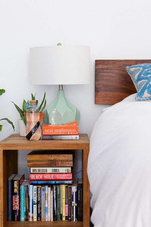 very pretty mint green lamp. love the mostly white bed and how much color the books stacked in the nightstand add.