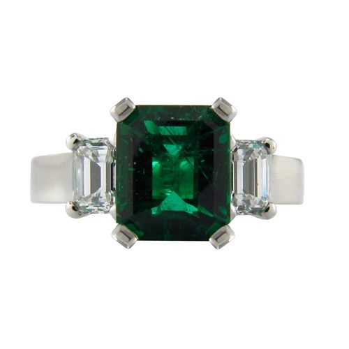 THREE STONE EMERALD & DIAMOND PLATINUM RING  An Emerald centre stone is flanked by two side diamonds. This three stone engagement ring is set in Platinum (R543)