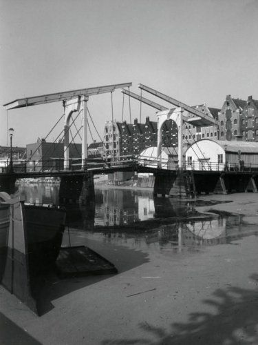 1942. Old bridge at the Prinseneiland in Amsterdam. The Prinseneiland is surrounded by the Prinseneilandsgracht, the Bickersgracht and Eilandsgracht. These form with the Bickerseiland and Realeneiland the Westelijke eilanden, 3 islands in the center of Amsterdam. From the beginning there were on the Westelijke eilanden about 900 warehouses, 28 bridges and many shipyards. Today most warehouses have been converted into apartments. Photo Spaarnestad / Van der Wielen #amsterdam #1942…