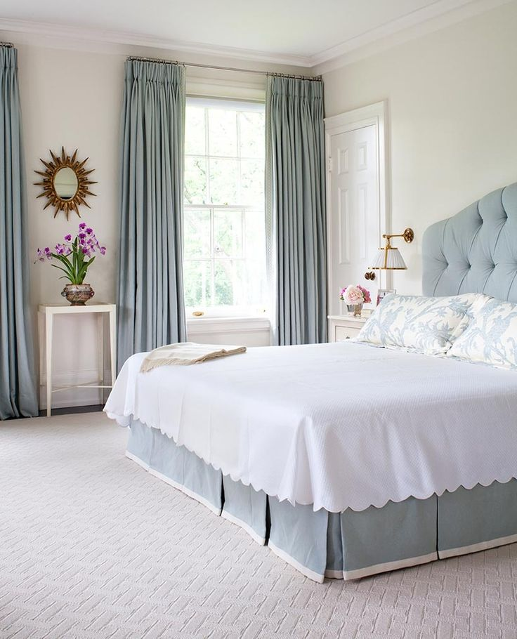 White bedroom with pale blue upholstered headboard and dusty blue draperies.
