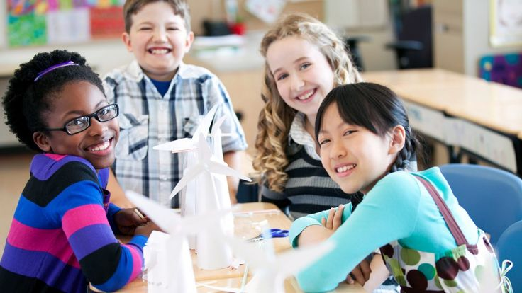 Four young students are smiling and sitting at two desks pushed together. Five paper-made windmills are on their desks.