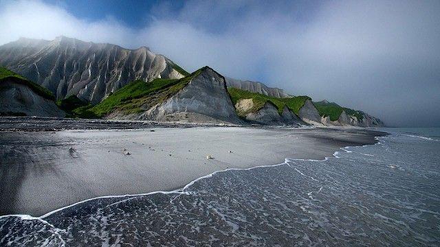 Южные Курилы, остров Итуруп. Вдоль берега залива Простор на много километров тянутся Белые скалы. Они состоят из очень легкой и мягкой пемзы, образовавшейся в результате колоссального вулканического извержения. Эта пемза размывается штормами Охотского моря и многочисленными речками, в результате скалы приобретают удивительные формы. У подножия этих скал - необычный черно-белый пляж, состоящий из смеси измельченной белой пемзы и черного лавового песка.