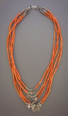 Layered orange beads adorned with ethnic sterling.