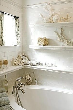 shelves line walls around bathtub in bathroom with seaside beach cottage theme shells sponges seashell home decor