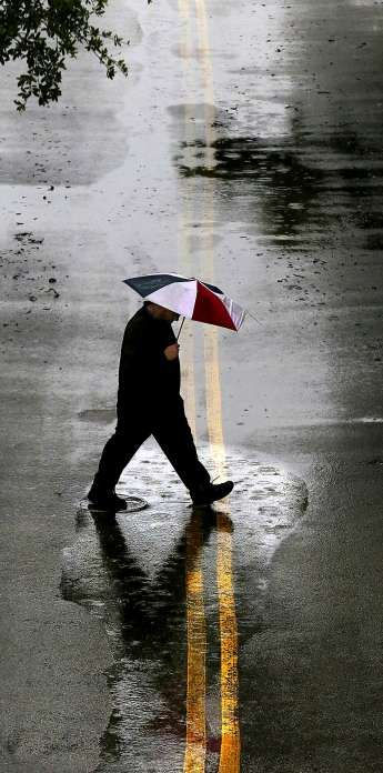 Struggle to find a serviceable umbrella and rain coat. Wait, do you even have an umbrella? It's got to be in the other closet somewhere... Photo: John Davenport, San Antonio Express-News