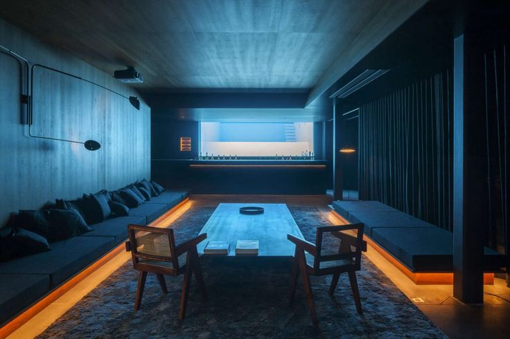 Underground bar receives most of its light from the window behind the bar which looks into the adjacent pool in this home in Ghent Belgium. [1050  700]