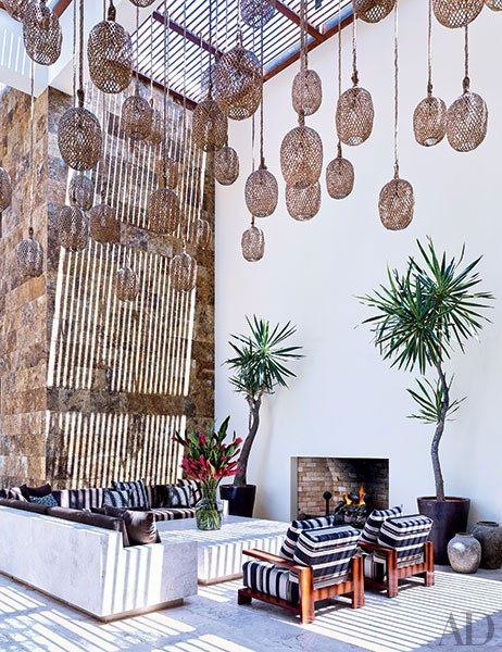 Twine-wrapped lanterns are suspended from the slatted canopy over George Clooney's courtyard in Los Cabos, Mexico, which features a Legorreta + Legorreta–designed cement-plaster table and L-shaped sofa, the latter topped with cushions in a Holly Hunt fabric and vintage pillows from John Robshaw
