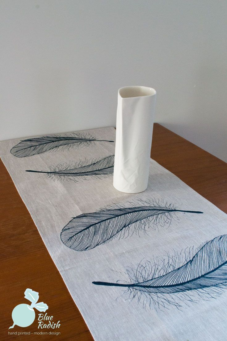 100% linen table runner in Feather design, handprinted in navy ink onto natural coloured linen. Measures approximately 150cm by 45cm.