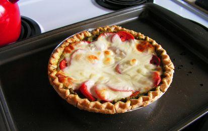 Torta salata al formaggio e pesto - Una squisita torta salata con la pasta brise' e tanto formaggio, con una speciale guarnizione di pomodori al forno e pesto alla genovese