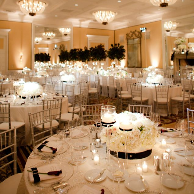 Low white floral centrepieces and candles decorate round for Black and white reception tables