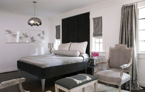 Gray and black bedroom features tall black headboard on black velvet bed dressed in platinum gray bedding, white and gray lattice pillows and white and gray bolster pillow illuminated by Metal Lotus Pendant flanking windows dressed in platinum gray roman shades over glass-top nightstands.