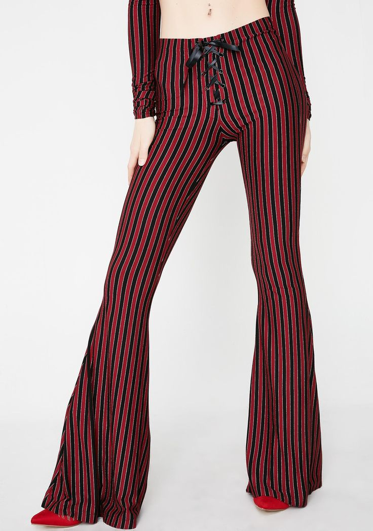 Current Mood Center Of The Ring Lace-Up Pants got all eyes on you. These red N' black striped pants have flowy legs, a mid rise fit, and a lace-up front closure.