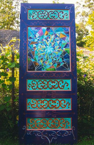 A vintage door painted bright colors with beautiful stained glass in the window. Love this!
