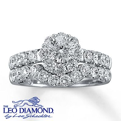This eye-catching engagement ring features a center round Leo Diamond and additional round Leo Diamonds that flow along the 14K white gold band. The matching wedding band features a dazzling array of round Leo Diamonds. These fine jewelry rings have a total diamond weight of 2 carats and are independently certified. The center diamond is laser-inscribed with a unique Gemscribe® serial number.