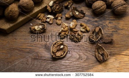Whole and cracked Walnuts on wooden chopping board and table.