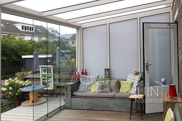 Een overdekte veranda buiten met een Gumax terrasoverkapping in mat crème met een polycarbonaat dak, een polycarbonaat zijwand, en glazen schuifdeuren. #tuin #schuifwanden #overkapping