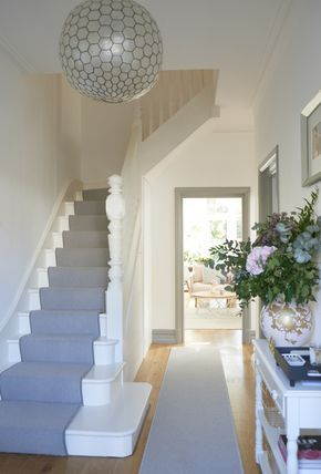 Fresh and bright hallway. Grey stair runner, and styled console table. Painted Farrow and Ball Manor House Gray, door frames and skirting. Feature ceiling light.