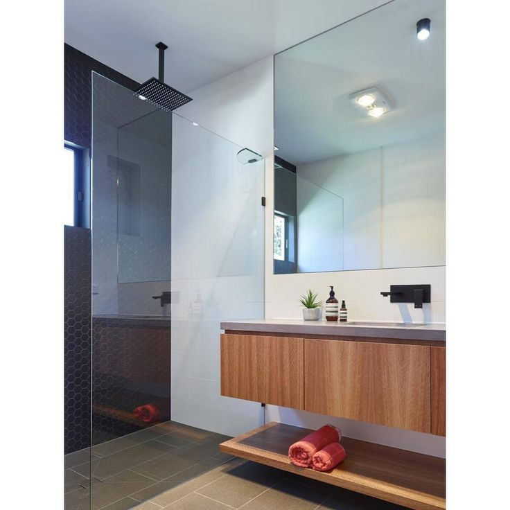 The detail in this striking bathroom design by @graya_construction is truly impressive. Each element has been carefully considered from the floating timber vanity, to the floor to ceiling tiles through to the contemporary square set ceilings and windows. This space is finished beautifully with a unique, contrasting matte black shower and tapware.  Did you know that the Meir range is now available from your local Reece store? Head to www.reece.com.au to find your closest store!