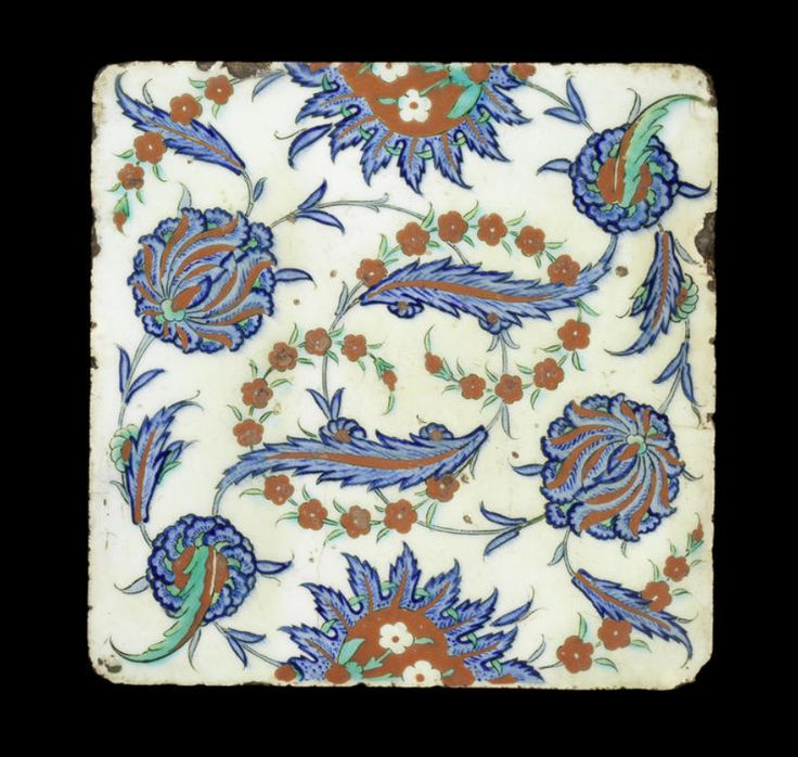 An Iznik pottery Tile  Turkey, circa 1575 decorated in cobalt-blue, raised red and green with black outlining on a white ground with a design of intersecting saz leaves and spiralling floral stems, peonies and roses, with two spiky half-flowers on either side