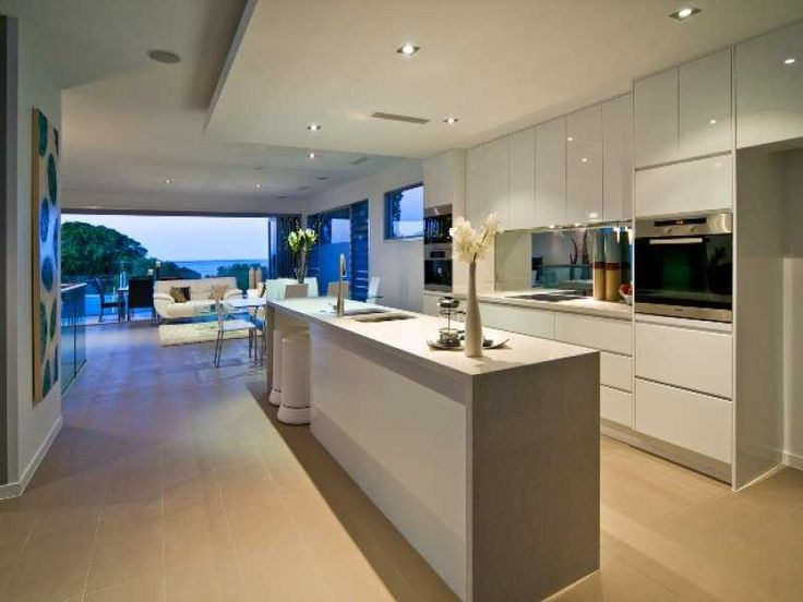 Kitchen inspiration: open plan kitchen dining area with white high gloss cabinets that reflect the light.