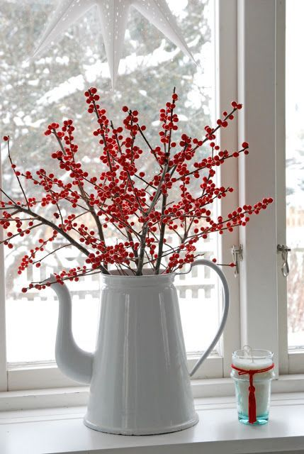 Simple white vase ( be creative: put an old tea pot to good use!) with ilex berries for a great pop of color.