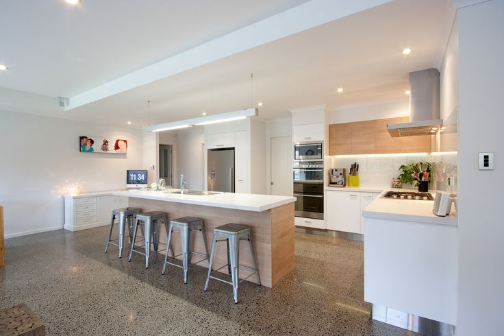 This modern kitchen is complete with a fully equipped scullery. A kitchen island with a timber clad base sits on top of a polished concrete floor. The timber cladding is continued on the upper cabinetry which features underneath lighting for the bench space below.