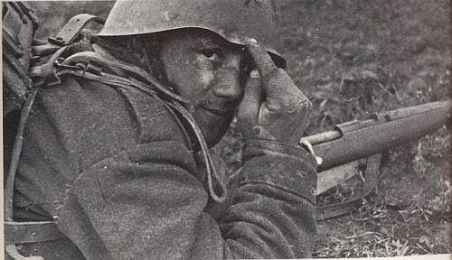 Italian soldier on the Eastern Front points to the spot where a bullet or ricochet hit, ca 1942