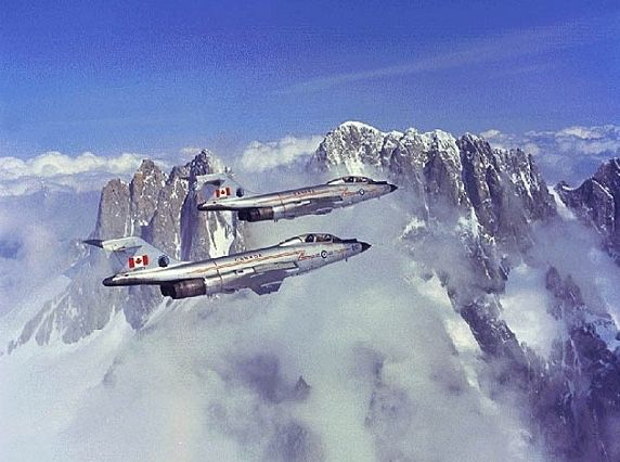 A pair of CF-101 Voodoos soar over the Canadian Mountains.