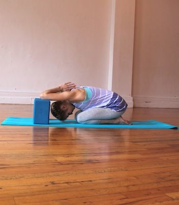 Shoulder opener on blocks yoga pose - place 2 blocks in front of you and place elbows on the blocks; press hands together in a prayer position, then release your head in between the blocks and reverse down back into prayer position. Stay for at least 10 deep breaths.