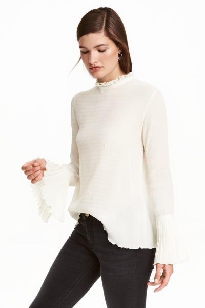 Bluzka z szerokimi rękawami: Bluzka z kreszowanego szyfonu o prostym kroju. Długie rozszerzane rękawy z plisowaniem u dołu i z brzegiem obszytym owerlokiem. Niewielka stójka z falbanką, na karku rozcięcie z guzikiem.