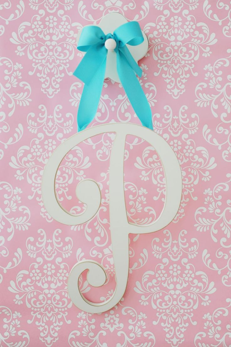 Antique White Large Cursive Letter with Ribbon by New Arrivals IncPersonalize your child's space with hand painted wooden wall letters from New Arrivals, Inc. Spell any name, word, or phrase that is unique to you! Select a ribbon for hanging and add the optional wall pegs to complete the look!Tori Swaim, owner and designer at New Arrivals, Inc., began the company with an idea for a box that would cleverly disguise those pesky, but necessary, plastic baby wipe containers. She created a…