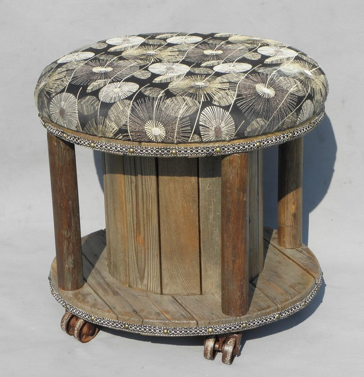 Up-cycled ottoman made from a small cable spool, using salvaged wooden pillars and iron wheels. Retro inspired flower fabric cushion with matching trim on the top and bottom, finished with upholstery tacks all around. Designed and built by Black Canyon Restorations. www.blackcanyonrestorations.com