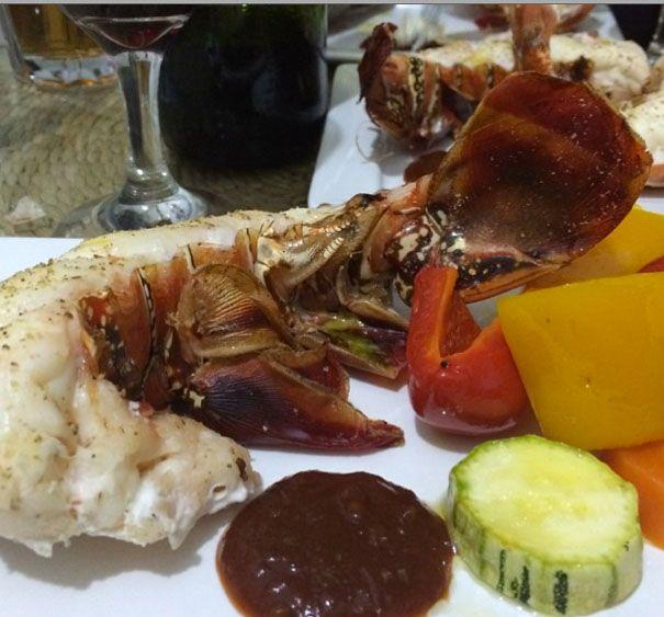 Cauda de lagosta cozida no forno, legumes cozidos no vapor e molho para crustáceos para complementar.