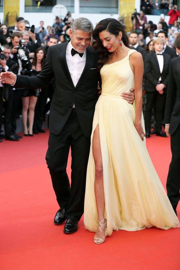 CANNES-DEBUT: George Clooneys smellvakre kone Amal Clooney er vant til å posere på den røde løperen, men har faktisk ikke vært på filmfestivalen i Cannes før i år. Og for en debut! Den vakre lysegule kjolen er fra Atelier Versace og den kjekke mannen ved siden av henne er selvsagt ektemannen. Foto: Afp