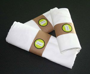 Rolled t-shirts with a recycled brown paper band that is held together with a sticker.
