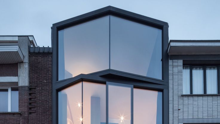 Windows angle out from the front of this family home in Ghent by Belgian architects Steven Vandenborre and Mias Sys, giving multiple perspectives on the street and city below.
