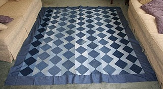 Quilt made from discarded blue jeans! Then she makes flowers out of the hems from the jeans!