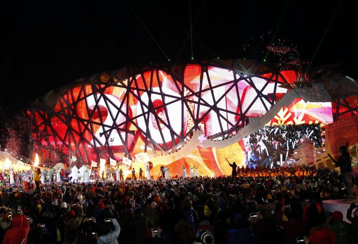 """Performers and attendees celebrate the arrival of the new year in front of the National Stadium, also known as the """"Bird's Nest"""", on which the year 2015 is projected, during a new year's countdown event celebrating the arrival of the new year and wishing in winning the bid to host the 2022 Winter Olympic Games, in Beijing January 1, 2015. REUTERS/Kim Kyung-Hoon"""