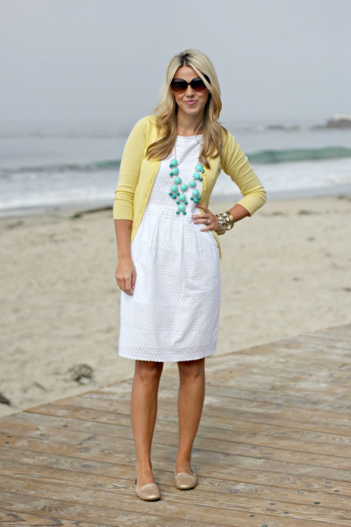 white dress with yellow cardigan and blue necklace