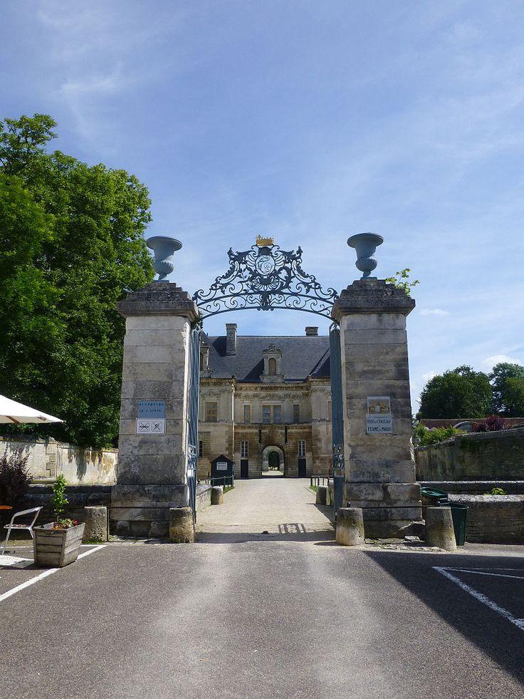 Château de Tanlay - 9) CHATEAU DE TANLAY, ARCHITECTURE EXTERIEURE: Une autre porte ornée de fleurs donne sur les jardins. Le quatrième mur fait face au château, auquel on accède par un pont précédé de deux obélisques de pierre.