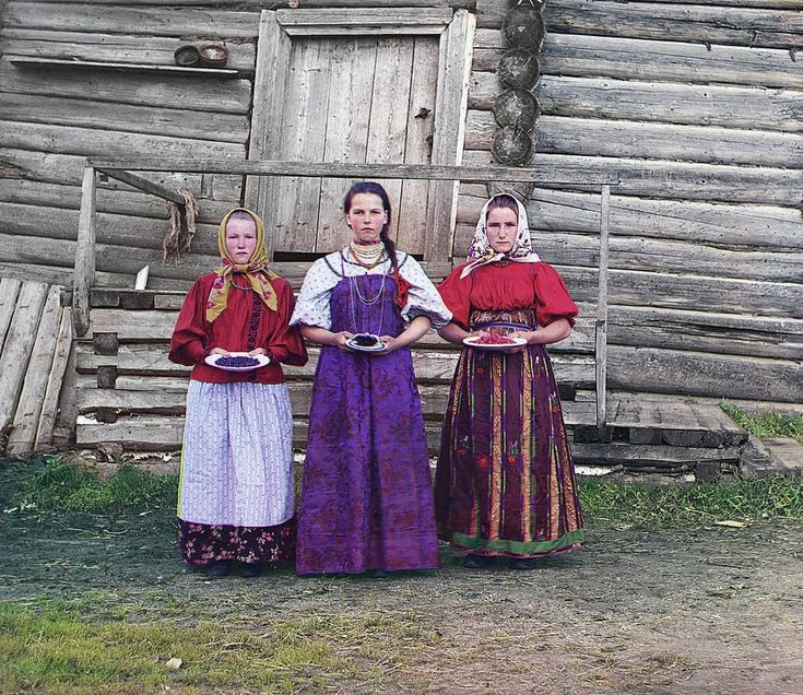 1909 Young Russian peasant women offer berries to visitors to their izba, a traditional wooden house, in a rural area along the Sheksna River near the small town of Kirillov.