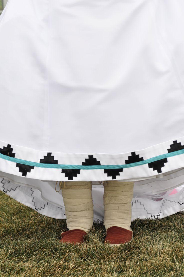 Navajo wedding basket design sewn to the bottom of a wedding dress with Navajo wrap around moccasins.