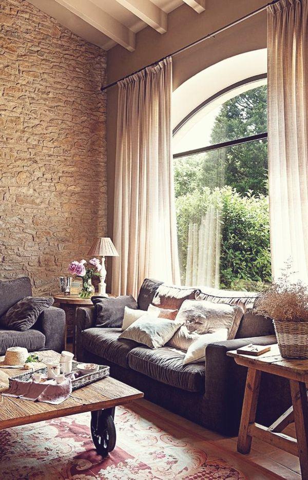 Fenêtre avec des rideaux beiges, mur en pierre