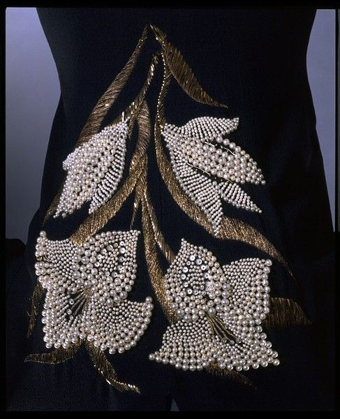 Elsa Schiaparelli (1890-1973) enjoyed the enormous publicity that her more bizarre creations generated, but her less provocative designs rarely caused a furore and have been somewhat neglected. She often referred to her simple black dresses and their versatility, and regularly wore black herself. Schiaparelli gave this dress to the V after her retirement. Here she composed a short-sleeved dress in matt black crepe. The extremely simple, fluid shape is relieved by a slashed neckline and a bo
