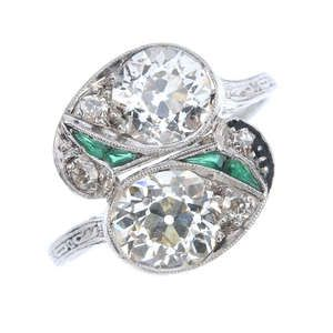LOT:452 | An Art Deco platinum diamond and emerald crossover ring
