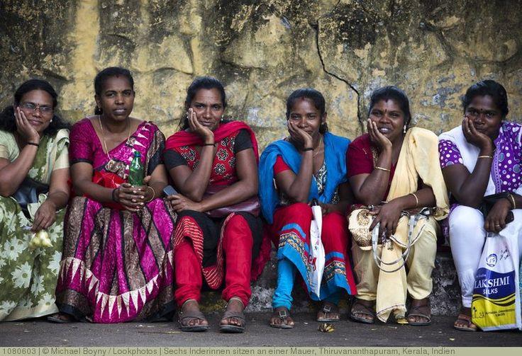 Sechs Inderinnen sitzen an einer Mauer, Thiruvananthapuram, Kerala, Indien